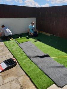 artifical grass in garden being layed